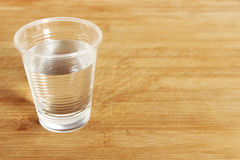 A plastic cup full of water on a chopping board Royalty Free Stock Photo