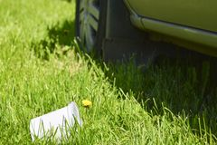 Plastic cup in the grass. The concept of environmental pollution, the rejection of plastic products, the use of packaging from. Natural materials stock photo