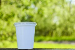 Plastic cup in the grass. The concept of environmental pollution, the rejection of plastic products, the use of packaging from. Natural materials royalty free stock photos