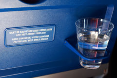 Plastic cup in the holder on airplane. Royalty Free Stock Image
