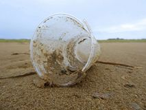 Plastic cup litter on beach. A discarded plastic drink cup lying on a sandy beach in England stock photography