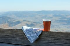 Plastic cup of natural hot tea and hat on wooden railing in mountains. Space for text stock photography