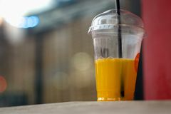 Plastic cup with orange juice standing on a surface on a street. City lights.Blured background stock image