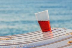 Plastic cup on a sunbed on a marine background. Plastic glass with a drink standing inclined on a sunbed on a blue sea background stock image