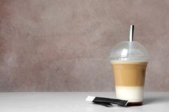 Plastic cup of tasty caramel macchiato on table stock image