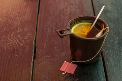 Plastic Cup with tea and lemon on wooden. Old table royalty free stock images