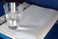 Plastic cup with water stands on magazine Royalty Free Stock Photos