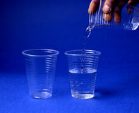 Plastic cup  on white. Pouring water on a Plastic cup on blue background Stock Photo