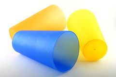 Yellow and blue plastic cups. Plastic cups, glasses or tumblers in bright yellow, orange and blue stock photo