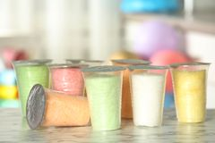 Plastic cups with cotton candy on table. Against blurred background royalty free stock photo