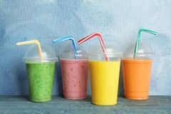 Plastic cups with delicious detox smoothies. On table royalty free stock images