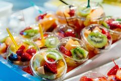 Plastic cups with delicious fruits for sale stock images