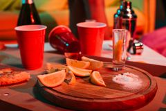 Plastic cups with drinks and sliced oranges. On party table stock photos