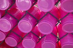 Plastic Cups Stuck in a Fence. A collection of empty pink plastic cups stuck in wire fencing royalty free stock photos