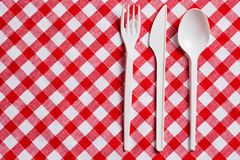 Plastic cutlery on checkered tablecloth Stock Photo