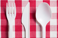 Plastic cutlery on checkered tablecloth Stock Photos