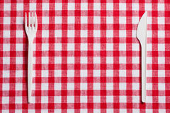 Plastic cutlery on checkered tablecloth Royalty Free Stock Images