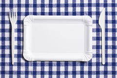 Plastic cutlery on checkered tablecloth Royalty Free Stock Image