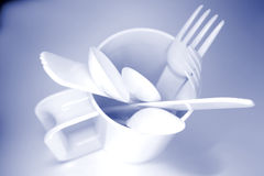 Plastic cutlery in cup. Isolated on light blue background stock image