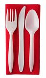 Plastic cutlery on red paper serviette. Standard white disposable cutlery as used in takeaways, picnics, parties etc. Festive red napkin Stock Photos