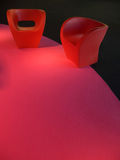 Plastic design couches on magenta carpet. Two red plastic design couches on magenta carpet Stock Image