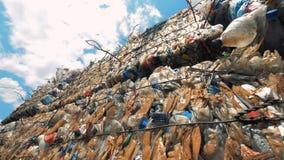 Plastic die huisvuil in kubieke stapels in openlucht wordt samengeperst stock footage