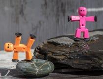 Plastic die stokcijfers op natte rotsen worden gesteld royalty-vrije stock foto