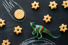 plastic dinosaur and cookies on the chalkboard, play and learning with the children royalty free stock images