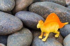 Plastic dinosaur on pebble stone. Background stock photography