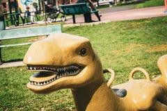 Plastic dinosaur swing in playground stock photography
