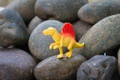 Plastic dinosaur toy. On pebble background stock photography