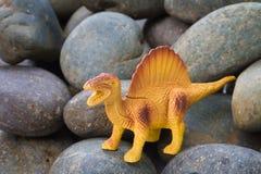 Plastic dinosaur toy. On pebble background royalty free stock images