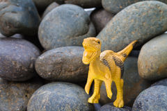 Plastic dinosaur toy. Plastic dinosaur on pebble stone, Velociraptor stock photos