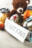Donation box with toys, clothes and food. Plastic donation box with toys, clothes and food, white grey background copy space Royalty Free Stock Photo
