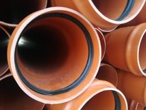 Plastic drain pipes pvc in a pile. Plastic drain pipes in a pile in the store, industry, industrial, tubes, pvc Royalty Free Stock Images