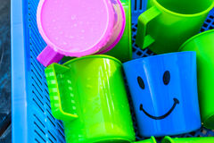 Plastic Drinking Water. Colorful plastic bowl of water placed in the basket. With a lovely smile Royalty Free Stock Photo