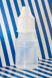 Plastic dropper bottle. Close up of opaque, white dropper bottle on blue and white striped background stock photo