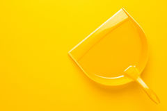 Plastic dustpan on yellow background Royalty Free Stock Photos