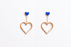 Plastic earrings heart. On a white background Royalty Free Stock Photography