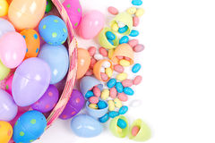 Plastic easter eggs and candy. Plastic easter eggs  filled with candy in a Easter basket on a white background Royalty Free Stock Photography