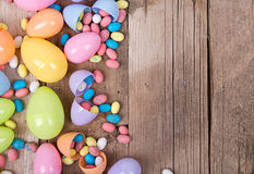 Plastic easter eggs and candy. Plastic easter eggs filled with candy on a wooden background Royalty Free Stock Photography