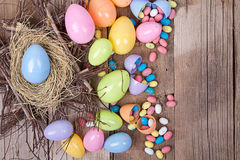 Plastic easter eggs and candy. Plastic easter eggs by nest filled with candy on a wooden background Royalty Free Stock Photo