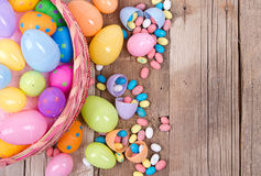 Plastic easter eggs and candy. Plastic easter eggs filled with candy in a Easter basket on a wooden background Stock Photos