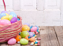 Plastic easter eggs and candy. Plastic easter eggs  with candy in a Easter basket on a wooden background Stock Images