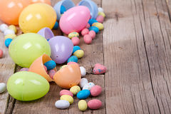 Plastic easter eggs and candy. Plastic easter eggs filled with candy on a wooden background Stock Photo
