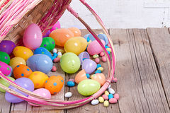 Plastic easter eggs and candy. Plastic easter eggs by nest filled with candy in a Easter basket on a wooden background Royalty Free Stock Photo
