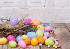Plastic easter eggs and candy. Plastic easter eggs by nest filled with candy on a woode background Stock Photography