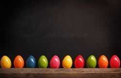 Plastic Easter eggs on a chalkboard. Colorful plastic Easter eggs in row on a black chalkboard with space for text or image Royalty Free Stock Photo