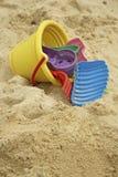 Plastic emmer en speelgoed op strand Stock Afbeeldingen