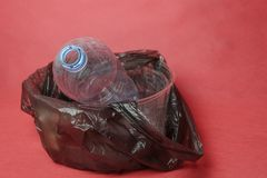 Plastic empty bottle in a black bag in container on red background. Concept of environmental pollution by plastic trash stock photography